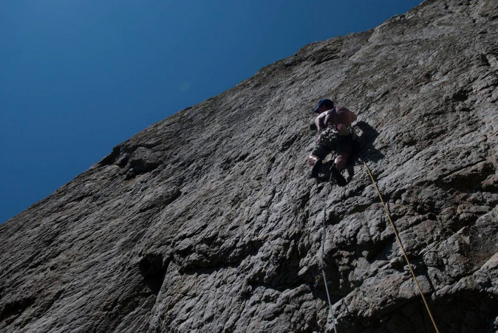 Simon Lake eye up the physical crux traverse to gain the flake on Blue Peter a classic E4 5c at North Stack Wall, Gogarth.