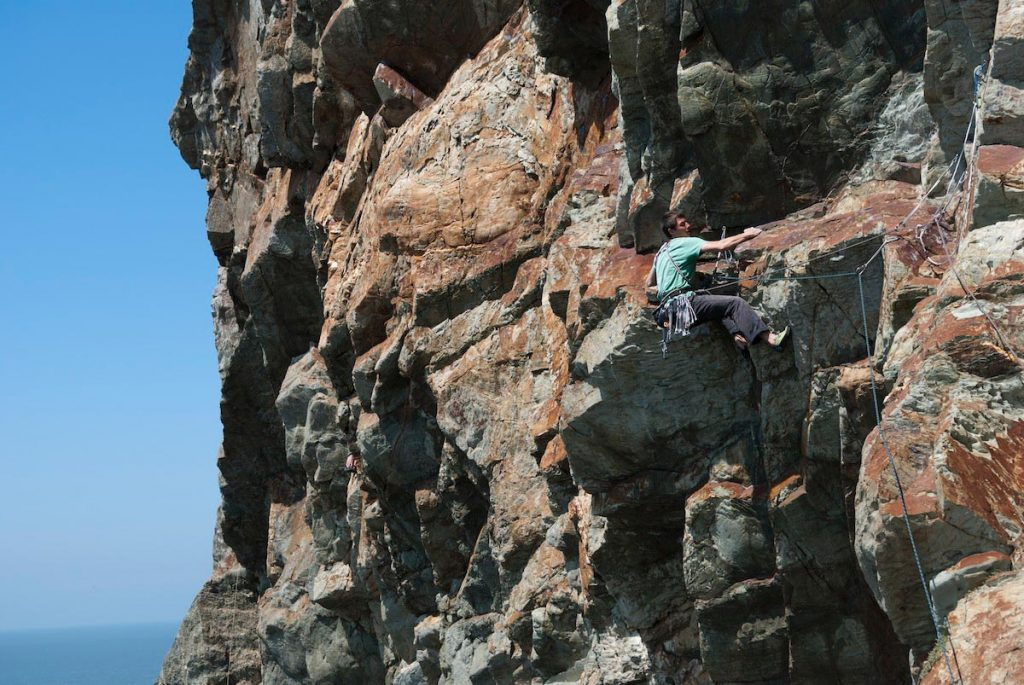 Dave Rudkin showing you the way on the Crux of Creeping Leema's second pitch, Yellow Walls, South Stack, Gogarth.