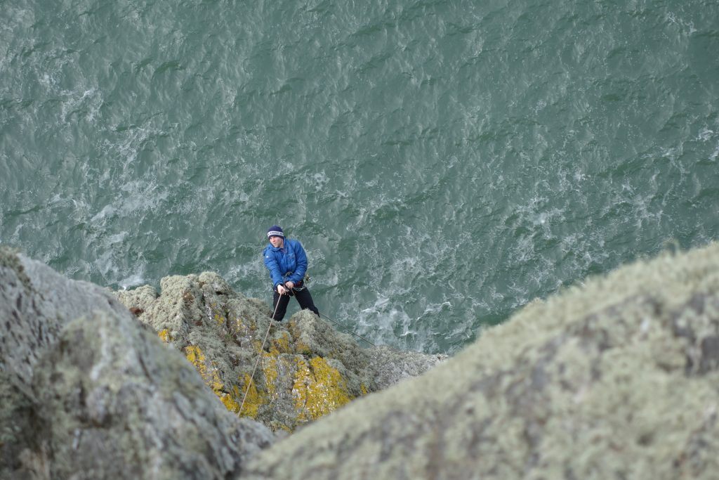 Alex Mason abseiling into Main Cliff to explore the possibilities of a new route.