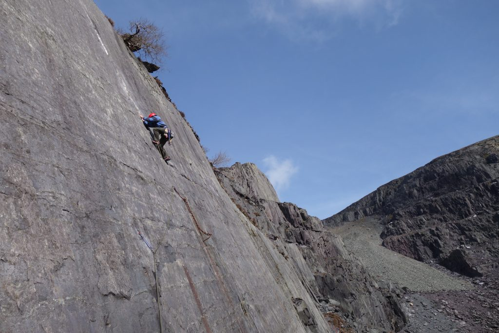 Gareth climbing the classic slate HVS Looning the Tube on one of our Private Coaching Courses, a fantastic slab with a mixture of bolts and trad gear.