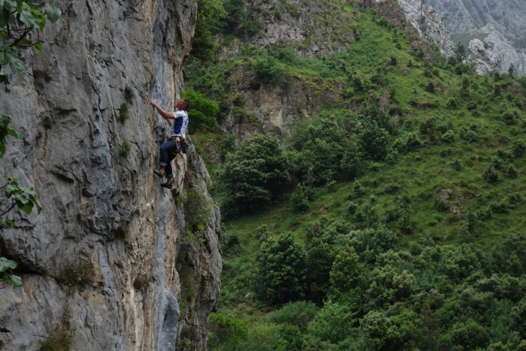 A climber on a classic 6c on the right side of Urdon in the Hermida Gorge, a fantastic sports climbing venue