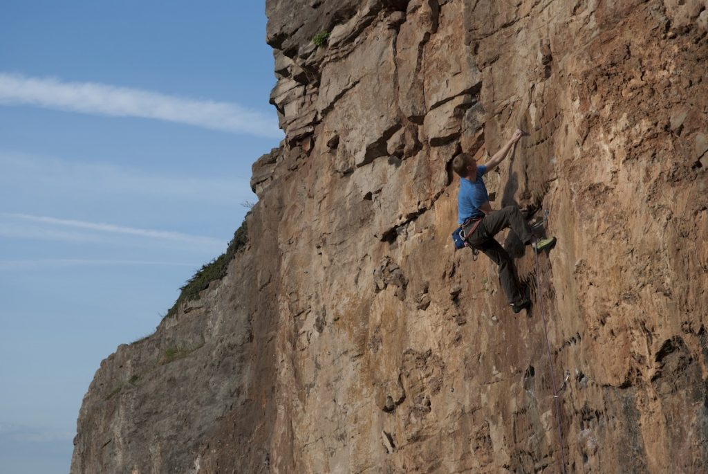 Richie Pullen on the mosdern classic Flowstone Shuffle a 6b at Peanmean Head which was only developed around 2010.