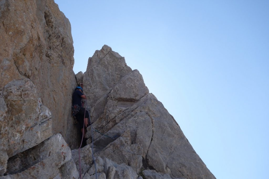 Josh Douglas on the short chimney section of pitch one of a Hard Severe that spirtals its way up a limestone tower in the High Picos Du Europa.