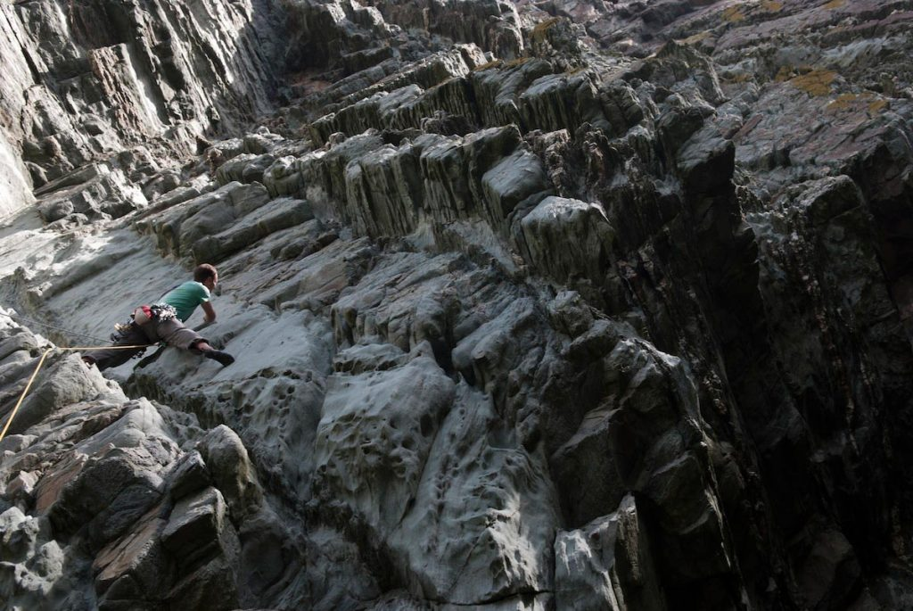 Simon Lake tackles the crux on the first pitch of Mousetrap, one of the finest E2, sea cliff adventures in the UK. Mousetrap Zawn, South Stack, Gogarth.
