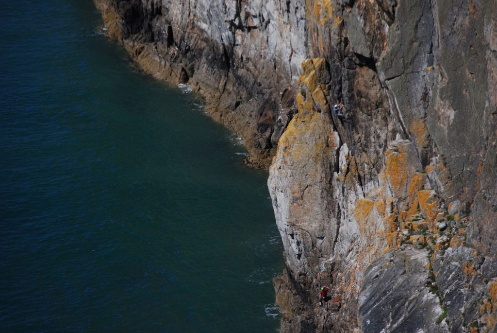 A climber (in Blue) tackles the classic Resolution Direct on Gogarth Main Cliff a classic E2.