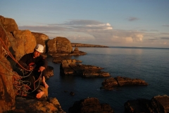 llion Morris enjoying comfort of the girdle ledge and the setting sun on Castell Helen, South Stack Gogarth.