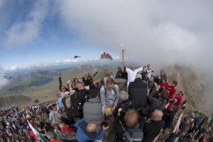 Sir Chris Bennington holds the Olympic Torch high on the Summit of Snowdon.