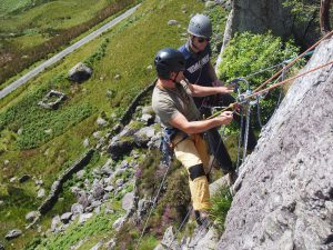 Learn to Teach Rock Climbing. Here looking at a transition from belaying up a climber to abseiling off a route.