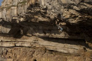 David Rudkin making the final campus move on Stiff Upper Lip at Pigeon's Cave , The Great Ormes