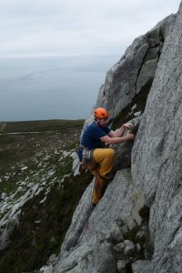 A climber on a Lead Climb Coaching Course climbing Pigeon Hole Crack on Holyhead Mountain