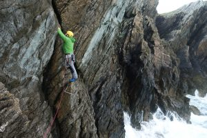 A climber on Private Coaching Day leads out across the start of Symphony Cracks (Diff), Rhoscolyn