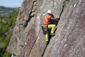 A client laybacking up the final strenuous pitch on Scratch, Vs, Tremadog, during a lead climbing coaching course.