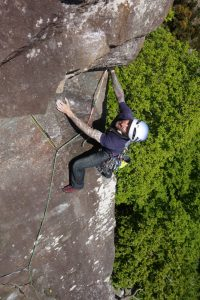 A cleint eyeing up the crux pull round the lip of Scratch Arete, HVS, during a private coaching course.