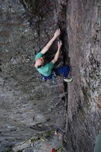 A man climbing the classic Cenotaph Corner, E1 on dinas Cromlech