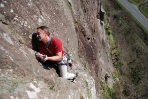 A climber finding a rest to palce gear on Grim Wall, A classic VS at tremadog.