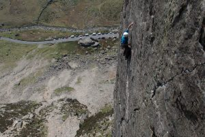 A climber powering their way up the final crack of Left Wall the ultimate E2 pitch in the Llanberis Pass.