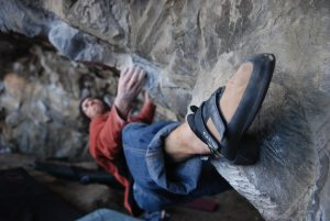 A climber heelhooking his way across the brutal Lou Ferrino, V9, Parisellas Cave, Great Ormes.