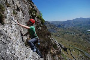 A climber eyeing up the final moves on Slick, Severe, Clogwyn Yr Oen, Moelwyns