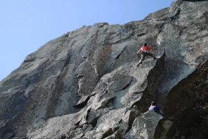 A climber having battled up the pod of Void, E4, is now faced with the boulder problem move to gain the continuation crack above!.
