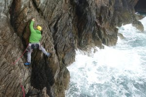 Sam traversing across to the base of the main slab on Symphony Crack at Rhoscolyn on a wild day