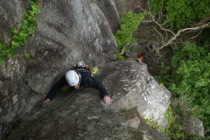 A client follows his climbing companion up the first pitch of Merlin.