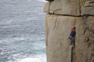 An unkown climber in the off width section of Demo Route, Sennen, Cornwall.