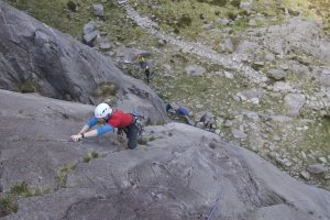 A climber on the technical first pitch of Charity on Idwal Slabs.